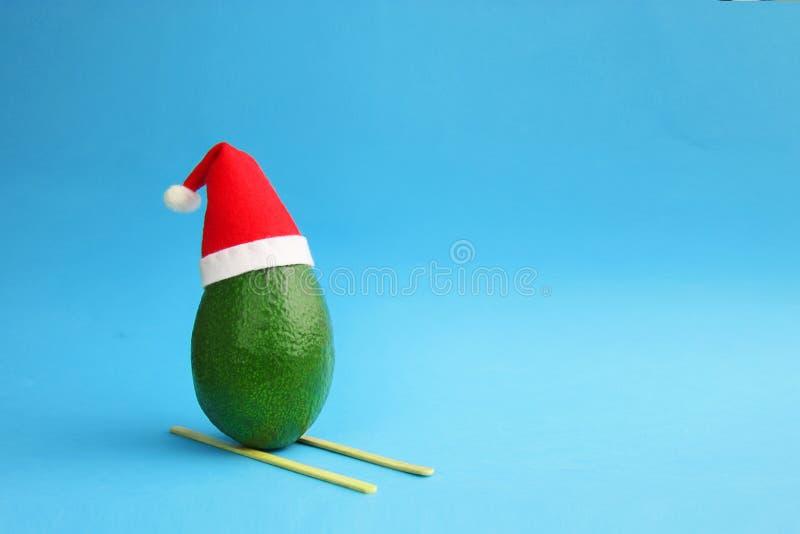 Julgarneringbakgrund med grön avokadoskidåkning för frsh i den santa hatten på ljus blå bakgrund Kortbegrepp closeup royaltyfri foto
