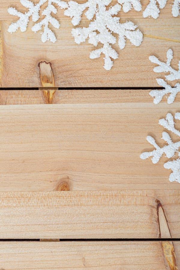 Julgarneringbakgrund och kopieringsutrymme Vita konstgjorda snöflingor på en trätabell closeup Lycklig glad jul arkivbild