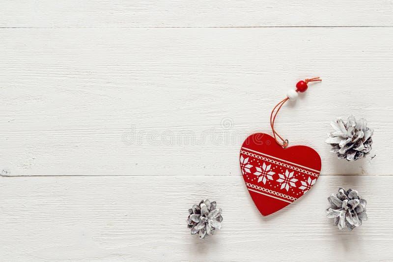Julgarneringhjärta och sörjer kottar på vita bräden Överkant v arkivfoton
