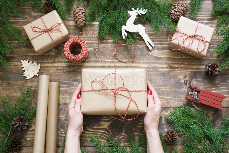 Julgiftbox och gåvor som slår in i hantverkpapper och dekor på träbräde Lekmanna- lägenhet Top beskådar arkivfoton