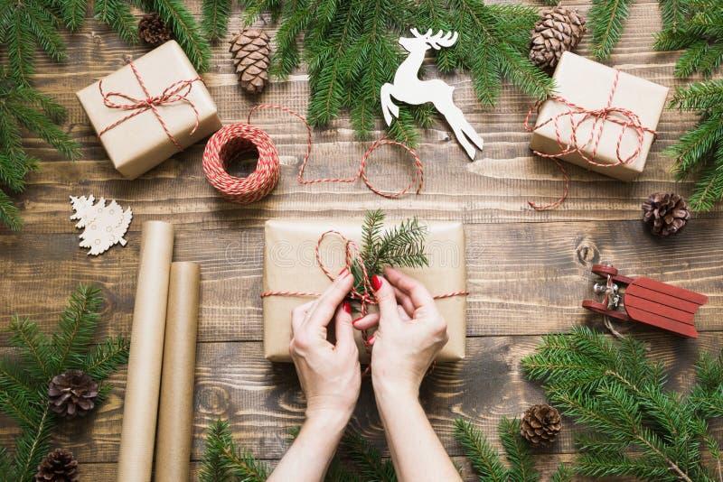 Julgiftbox och närvarande askar som slår in i hantverkpapper och dekor på träbräde arkivbild