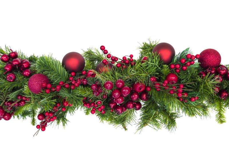 Julgirland med röda bär och struntsaker som isoleras på vit royaltyfri bild
