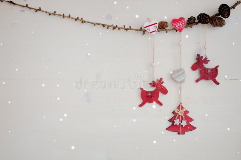 Julgirland med röda trähjortar, hjärtor, julgranen och kottar fotografering för bildbyråer