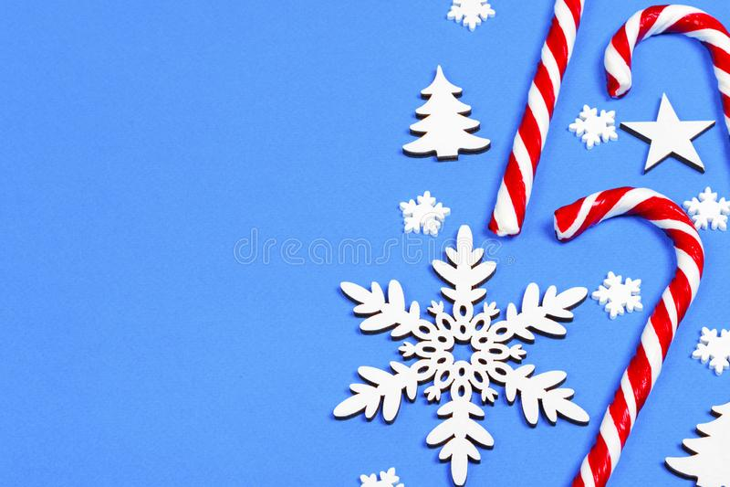 Julgodisrottingen låg jämnt i rad på blå bakgrund med den dekorativa snöflingan och stjärnan Lekmanna- och bästa sikt för lägenhe arkivbilder