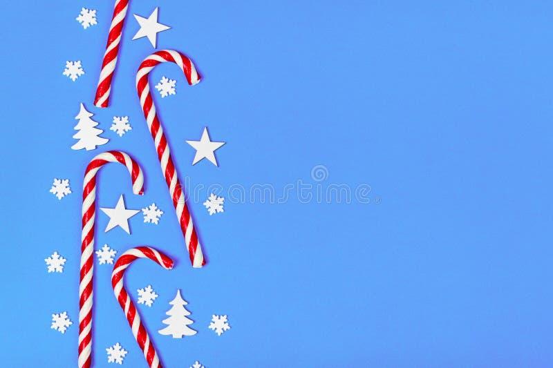 Julgodisrottingen låg jämnt i rad på blå bakgrund med den dekorativa snöflingan och stjärnan Lekmanna- och bästa sikt för lägenhe royaltyfri fotografi