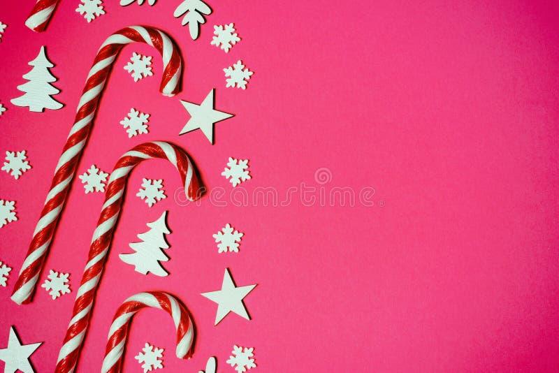 Julgodisrottingen låg jämnt i rad på rosa bakgrund med den dekorativa snöflingan och stjärnan Lekmanna- och bästa sikt för lägenh arkivbilder
