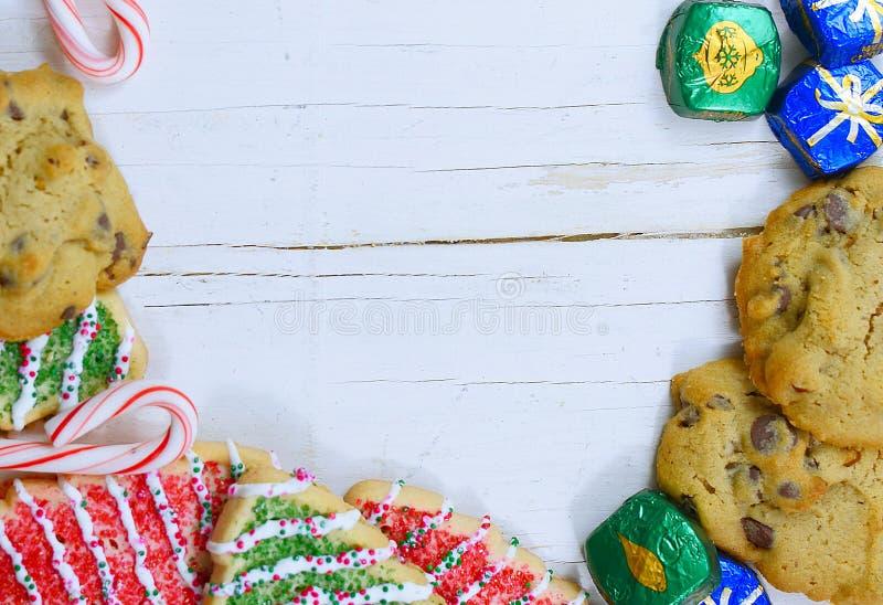 Julgränsen för sötsaker, inklusive kakor, pepparfärger och choklad på en rustik träbakgrund arkivbild
