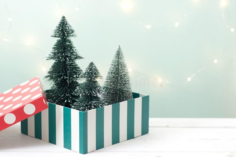 Julgran i gåvaask på trätabellen över suddighetsbokehljus - grön bakgrund arkivbilder