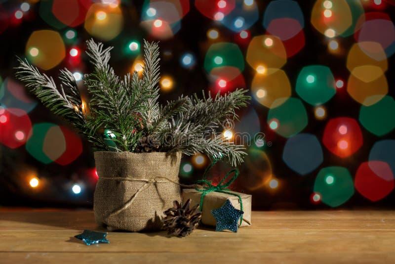 Julgran i kruka- och gåvaask i inpackningspapper, stjärnor och pinecone på bakgrund av färgcirklar royaltyfria bilder