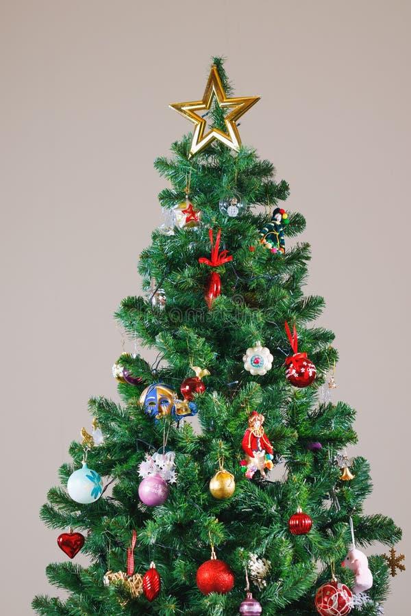 Julgran med den guld- stjärnan och garneringar arkivbild