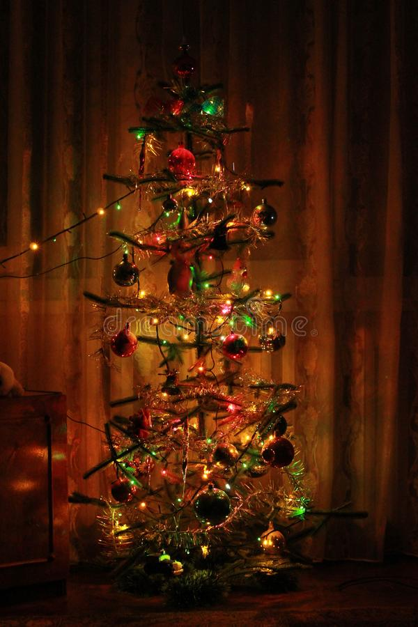 Julgran med garneringar och girlander i hemmet arkivbild