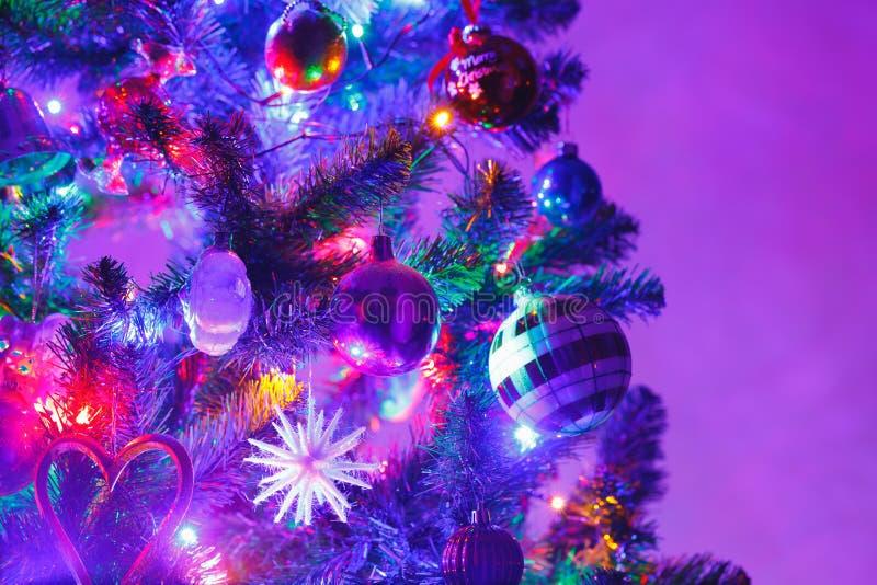 Julgran med garneringar och purpurfärgad belysning royaltyfria bilder