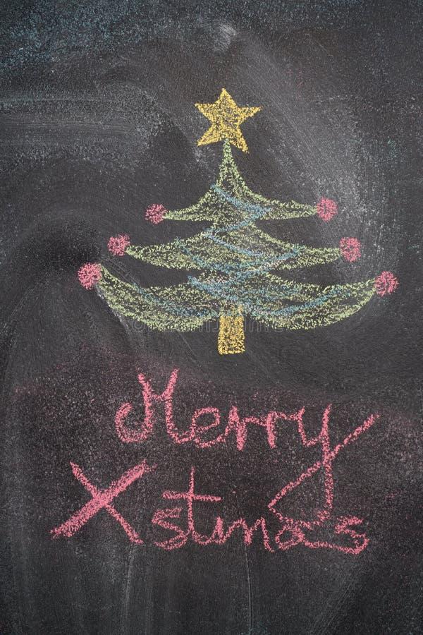 Julgran med glad Xmas-handstil på den svarta svart tavlan arkivbilder