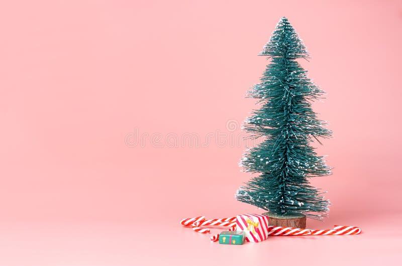 Julgran med godisrottingen på studiobakgrund för pastellfärgade rosa färger arkivbild