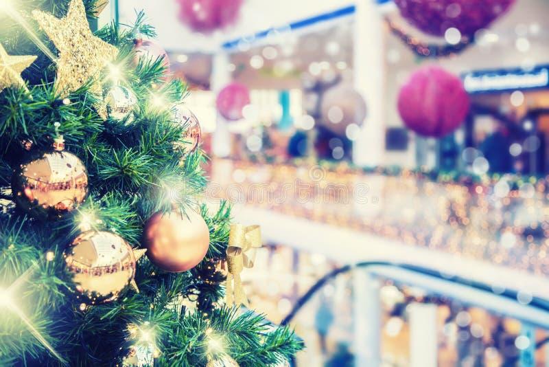Julgran med guld- garnering i shoppinggalleria arkivfoto