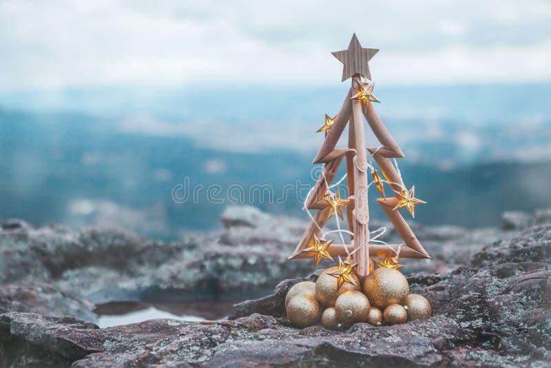 Julgran med guld- ljus och bergbakgrunden royaltyfria foton