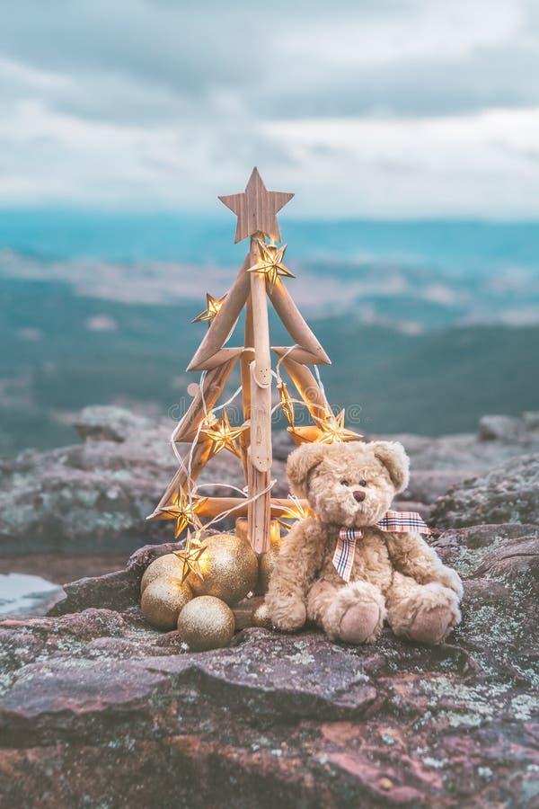 Julgran med guld- stjärnaljus mot bergbakgrunden arkivbilder