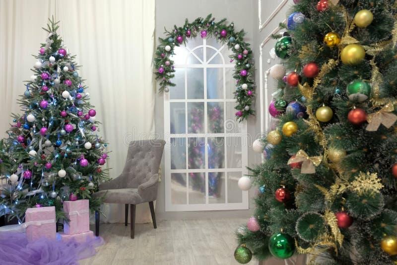 Julgran med kulöra bollar och girlander Tomt rum som dekoreras i nytt års stil Traditionell dekor för att fira arkivbilder