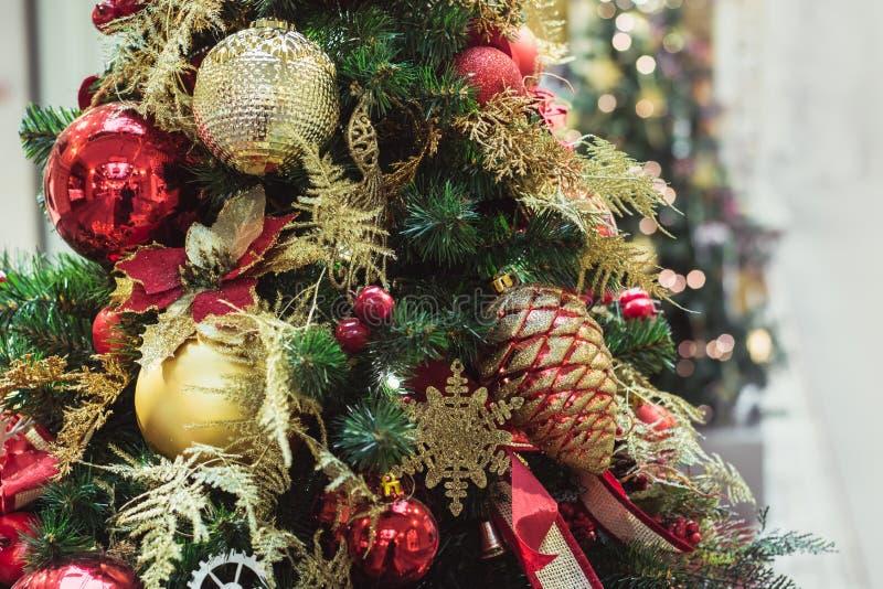 Julgran med röda och guld- blommadekorinre xmas close upp arkivfoto