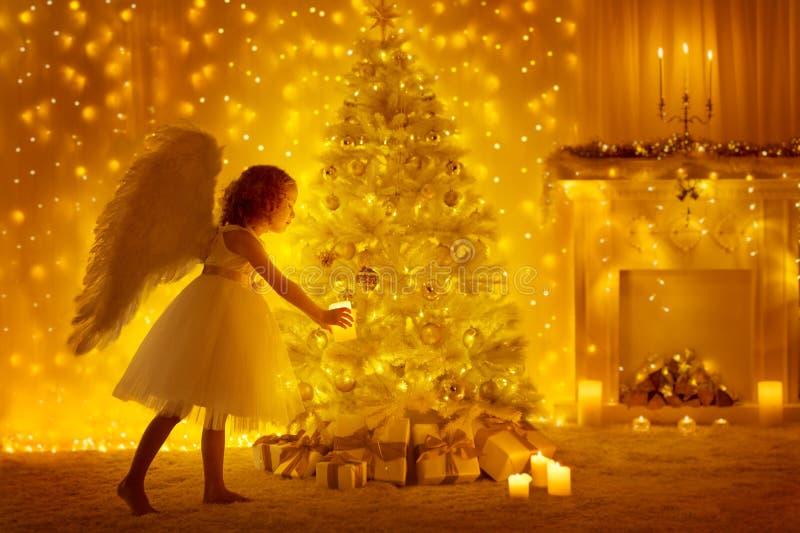 Julgran och Angel Child med stearinljuset, flickan och gåvor arkivfoton
