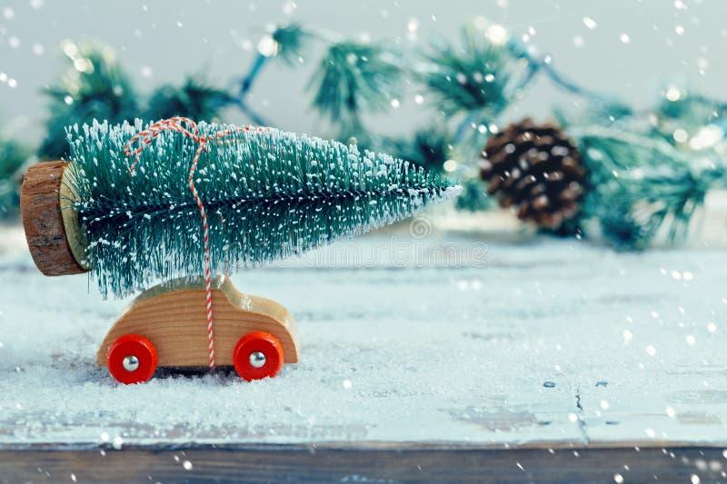 Julgran på leksakbilen över snöbakgrund Julferieberöm arkivbild