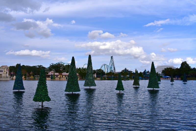 Julgran på sjön, berg-och dalbanan och den färgrika diversehandeln på molnig himmel på det Seaworld temat arkivbild