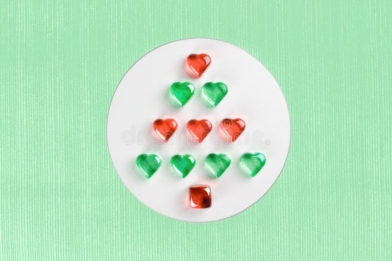 Julgran som göras av hjärtor för rött och grönt exponeringsglas som lägger i den vita cirkeln på texturerad mintkaramellbakgrund royaltyfri fotografi