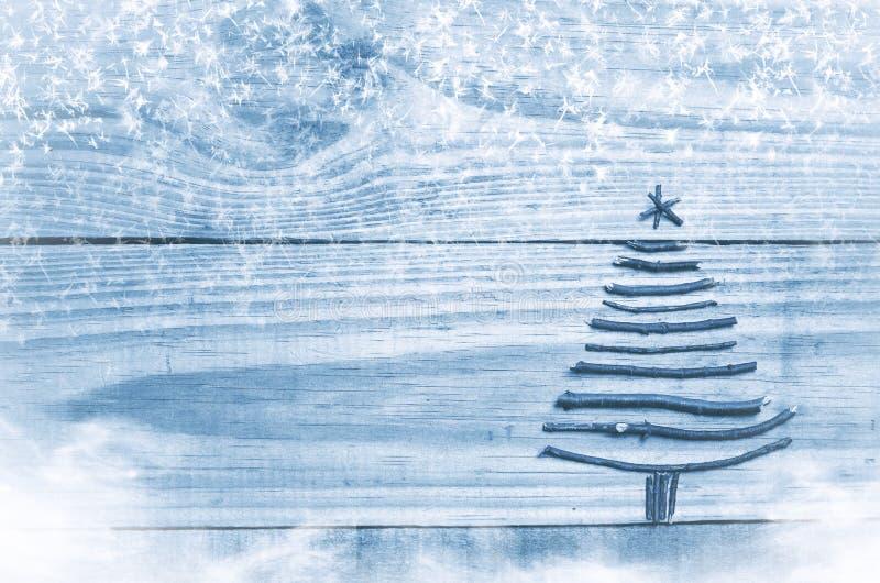 Julgran som göras från torra pinnar på trä blå bakgrund Snö- och snöluftvärnseldbild Julgranprydnad med stjärnan