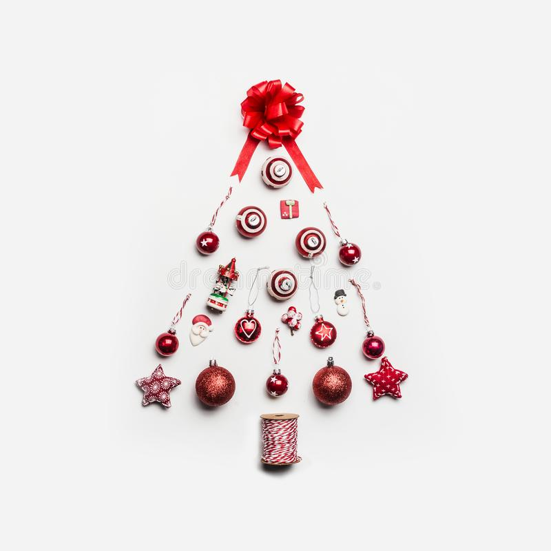 Julgran som göras med olika festliga ferieobjekt: bollar gåva, band, jultomten, garneringar, stjärna, snögubbe på vit arkivbild