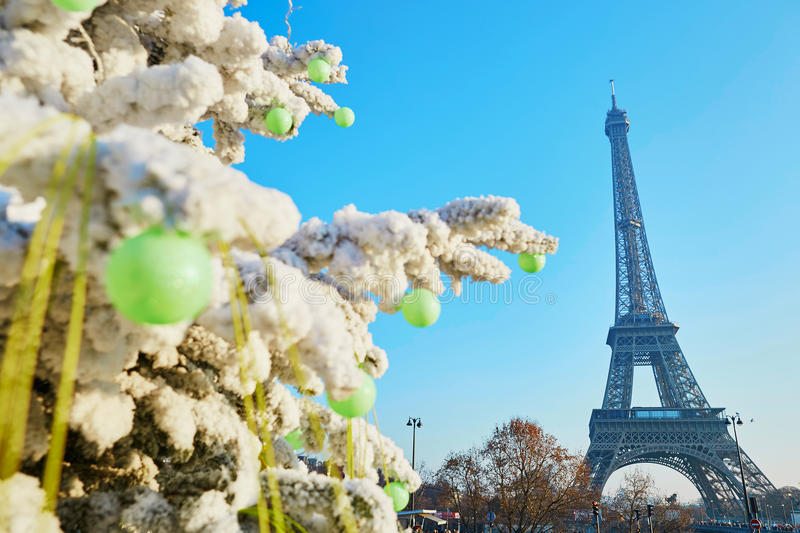 Julgran som täckas med snö nära Eiffeltorn i Paris royaltyfri fotografi