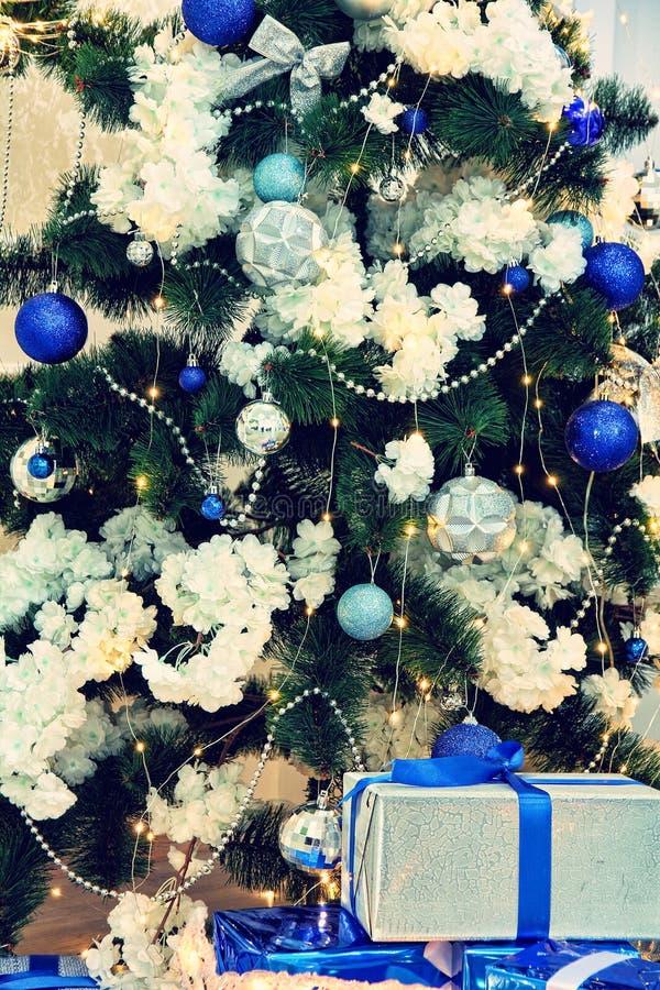 Julgran-träd, julgarneringar och gåvor som tätt tas upp på ett grönt gran-träd royaltyfria foton
