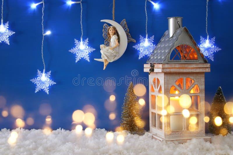 Julgranar den gamla lyktan, snöflingor försilvrar girlandljus, fen på månen över snön och blåttbakgrund fotografering för bildbyråer