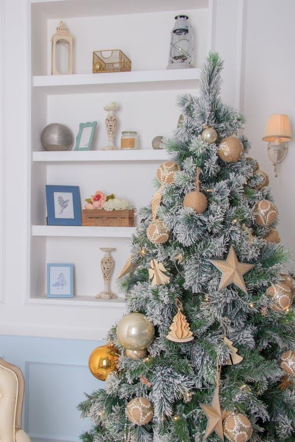 Julgranbakgrund och julpynt i den moderna inre Vita och guld- bollar på grön päls royaltyfri bild