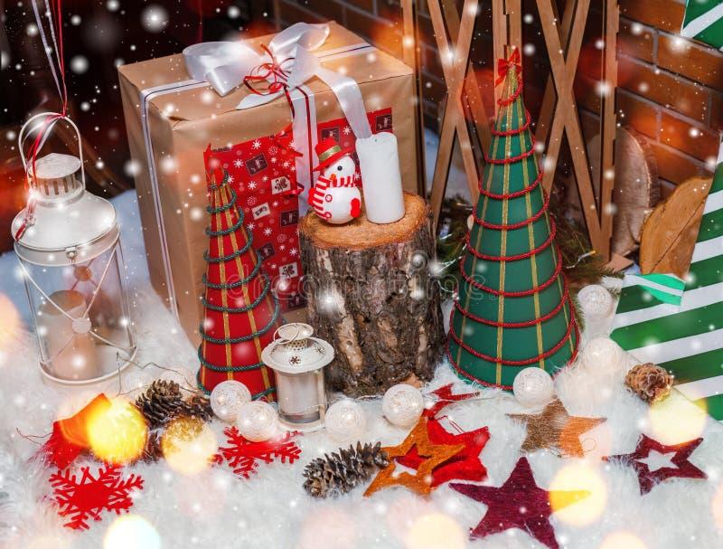 Julgranbakgrund och julpynt med snö, gåvor, suddigt som gristrar lyckligt nytt år för kort Vinterferie och Xm arkivfoton