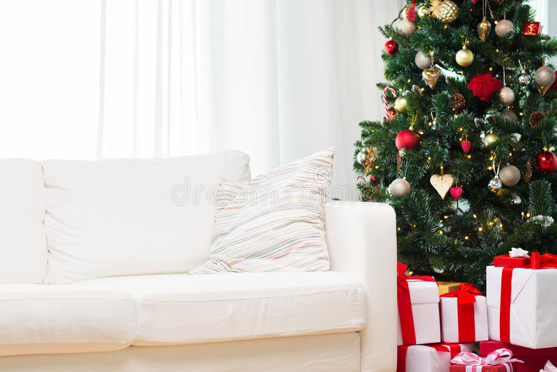 Julgranen, gåvaaskar och soffan hyr rum hemma royaltyfri bild