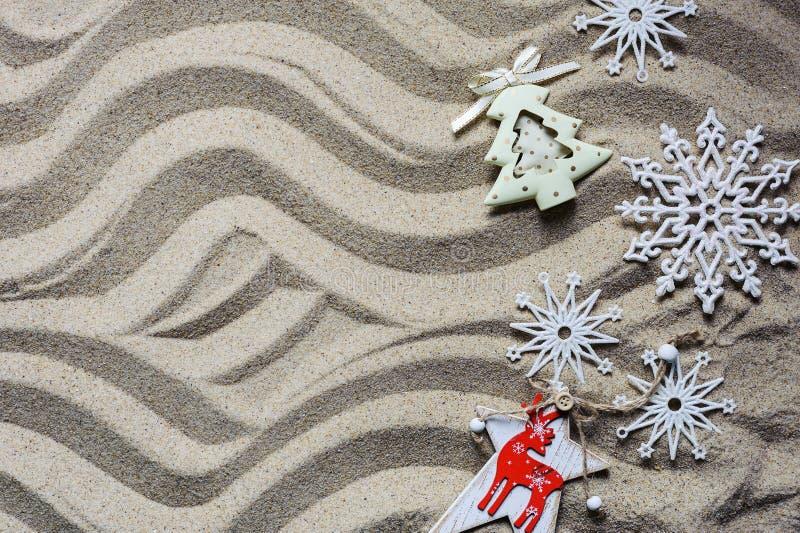 Julgranen och snöflingor ligger på havssanden arkivfoto