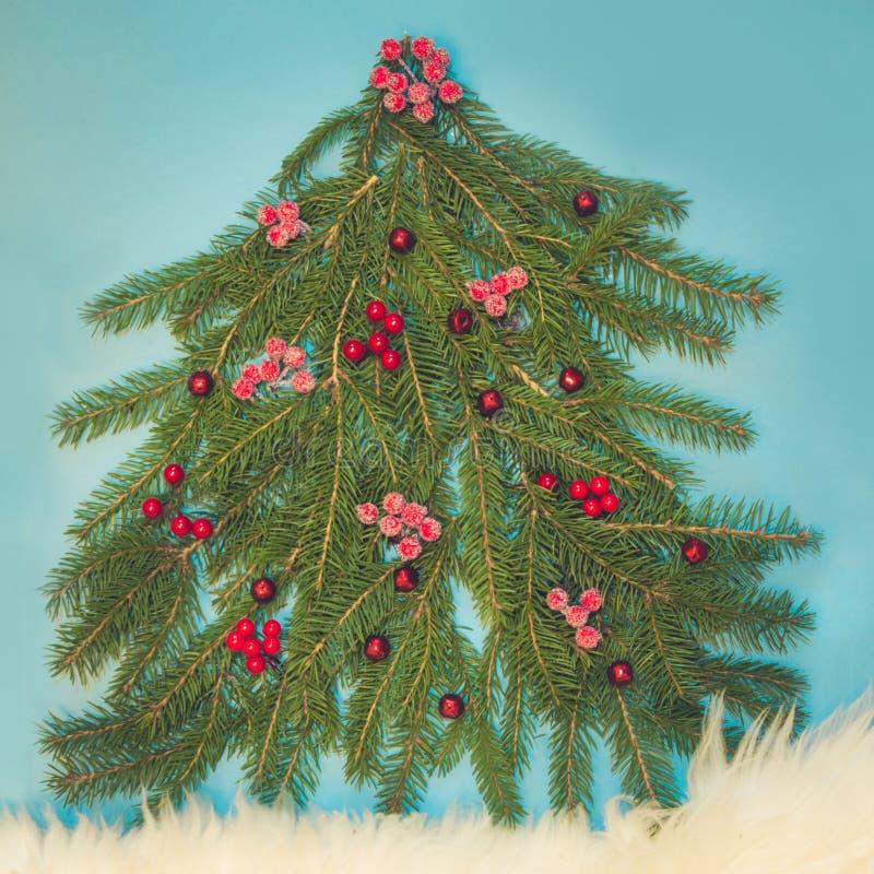 Julgranen som gjordes av prydlig filial, dekorerade röda järnekbär på blått Top beskådar Xmas-sammansättning royaltyfria foton