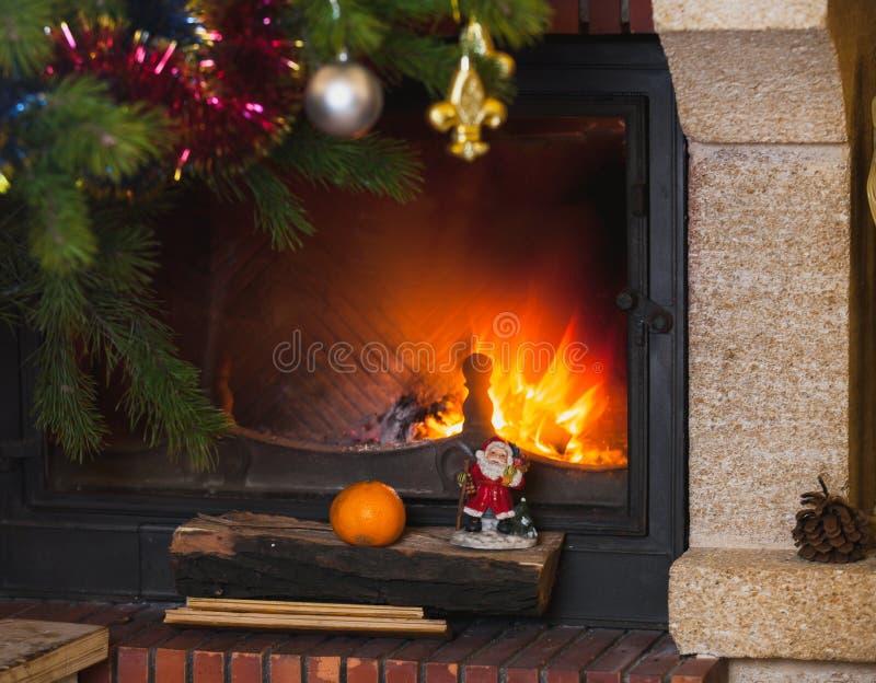 Julgranen står framme av spisen med bränningfirewoo arkivfoton