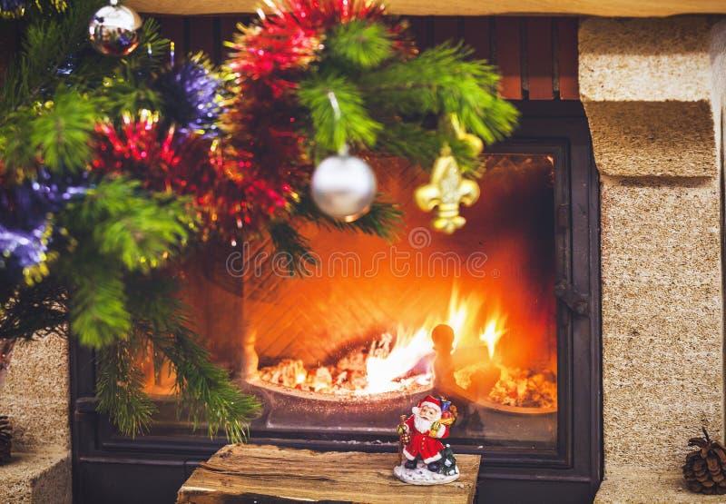 Julgranen står framme av spisen med brinnande vedträ royaltyfria foton