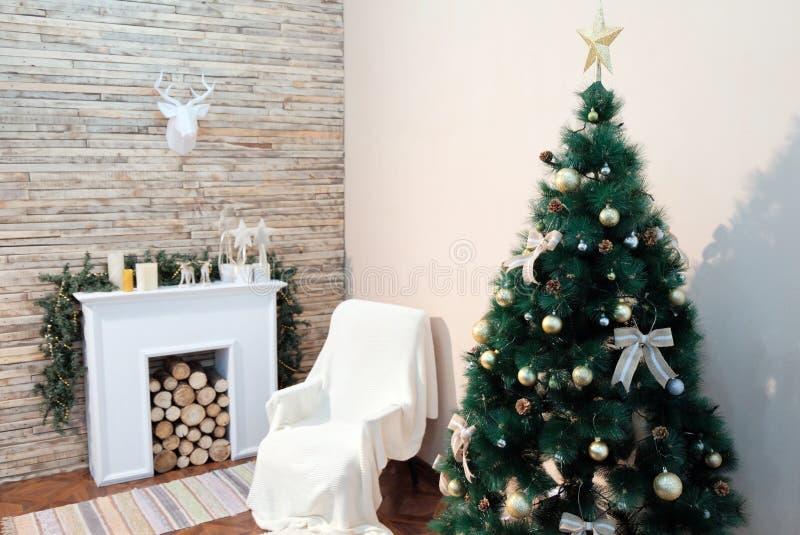 Julgranen står nära nattduksbordet och spisen mot den vita väggen Lyckligt nytt år för tema Hängande nolla för pappers- hjorthuvu arkivfoton