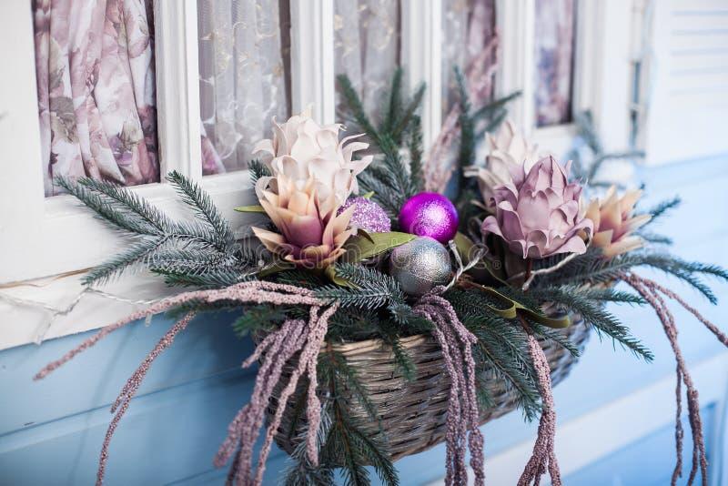 Julgranfilialer och blommor i korgen fotografering för bildbyråer