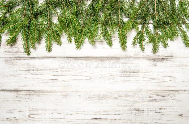Julgranfilialer på trätextur vinter för snow för pojkeferielay royaltyfri foto