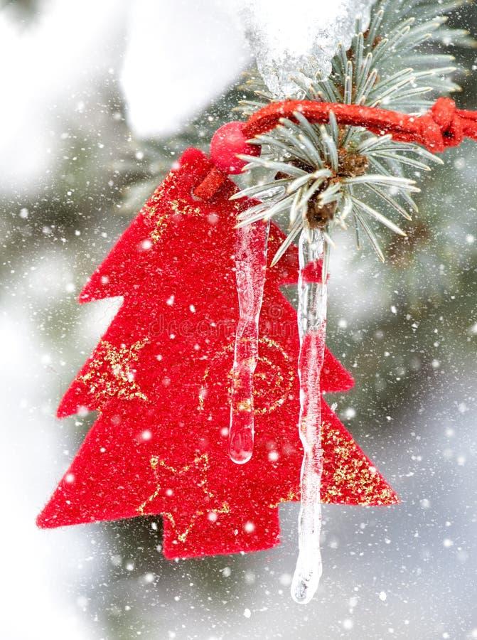 Julgranleksak i snöfall med istappen royaltyfria bilder
