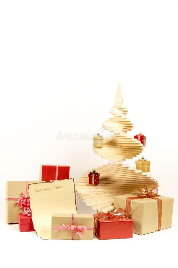 Julgranträ med feriegåvaaskar dekorerade med bandet, och bokstaven till Santa Claus isolerade på vit bakgrund royaltyfri fotografi