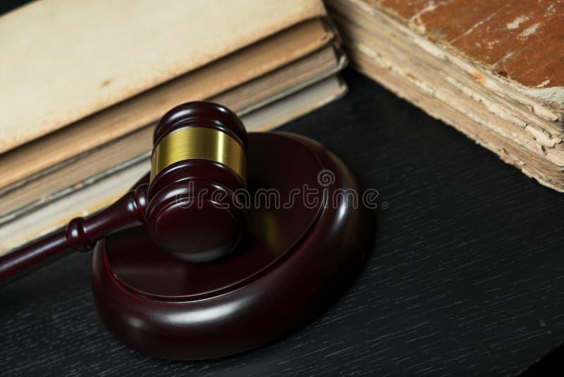 Julgue o martelo ao lado da pilha dos livros no fundo de madeira imagens de stock royalty free
