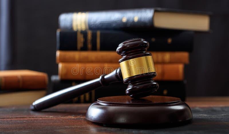Julgue o martelo em uma mesa de madeira, fundo dos livros de lei
