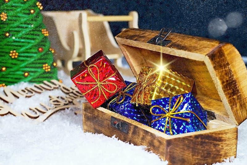 Julhälsningar för jultid Snöflingor som mycket täckas med aftonhimmel med den Santa Claus släden, julgranen och bröstkorgen arkivfoton