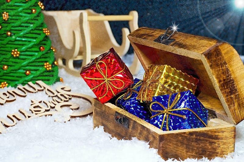 Julhälsningar för jultid Snöflingor som mycket täckas med aftonhimmel med den Santa Claus släden, julgranen och bröstkorgen royaltyfri bild