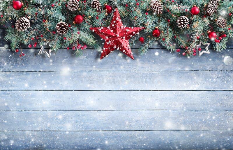 Julhälsningkort - granfilial och garnering på snöig fotografering för bildbyråer