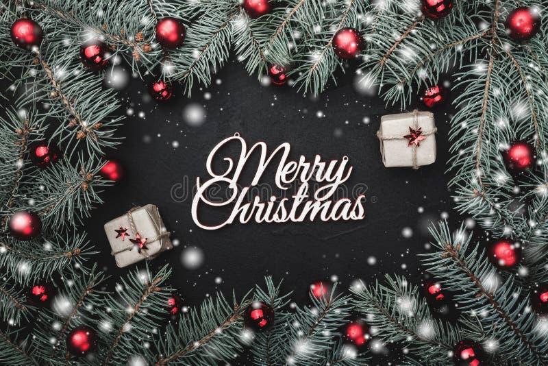 Julhälsningkort i svart bakgrund ramen av granfilialer smyckade med röda bollar Snöeffekt och dekorativa gåvor royaltyfri bild